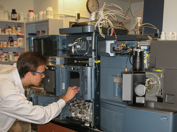 Tomas adjusts one of the instruments of the chemical biology set of resources in the Nodwell Lab.