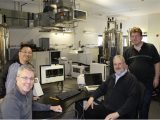 The photo shows Scott Prosser, Oliver Ernst, and senior research scientists, Libin Ye and Ned van Eps, discussing recent results in the lab.